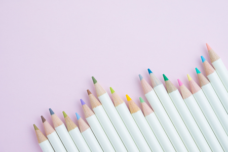 Various color pencils with white wooden handle on sweet pastel pink background using as art, education and adult coloring meditation.