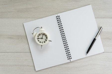 Opening white blank page paper book with pen and alarm clock on light grey wooden table background.