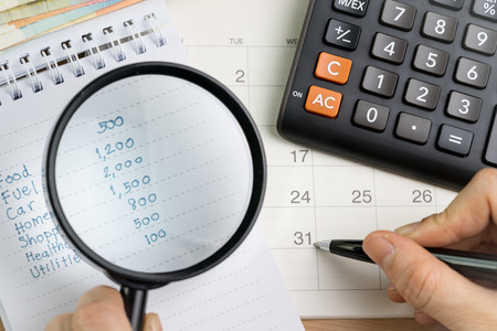 Personal expense calculation or pay day concept, magnifying glass on list of numbers of expenses with pen pointing on month end date and calculator.