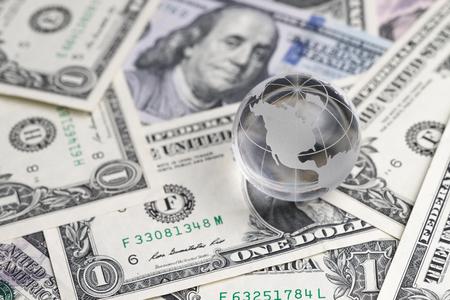 United States financial anti globalization or center of world economic concept, shiny decoration glass globe on pile of US dollar banknotes. Standard-Bild