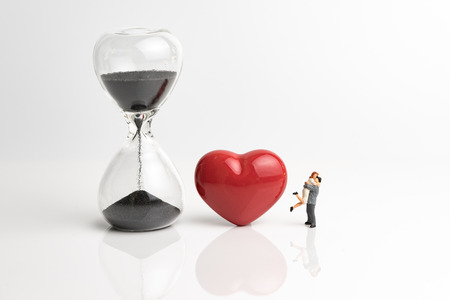 Time prove love for couple concept, with sandglass or hourglass, red shiny ceramic heart shape and miniature couple holding each other on white background. Standard-Bild