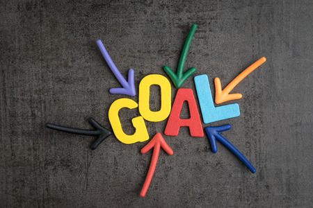 Business success target or goals concept, colorful wooden alphabets GOAL at the center with pointing arrow magnet on black chalkboard cement wall.
