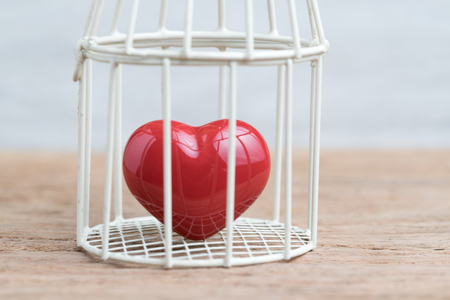 Love, romance or anchoring in the past concept, closed up of red heart inside the miniature birdcage, can be used as no freedom for relationship. Standard-Bild