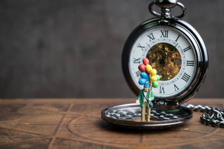 Happy retirement time countdown concept, senior old man holding balloons standing on vintage pocket watch in soft tone, can be use as good health of aged people. Standard-Bild