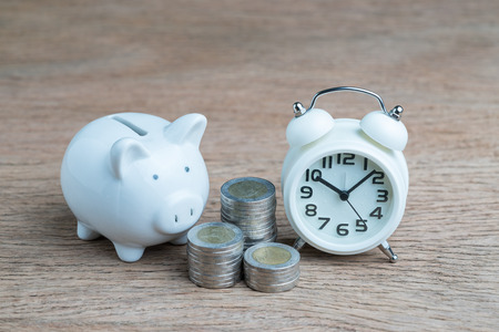 White piggy bank, coins stacked and alarm clock on wood table, financial long term saving money concept,  compound interest of investment awareness. Standard-Bild