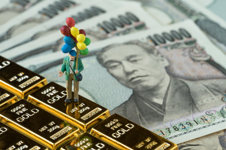 Financial freedom or happy retirement concept, miniature figure happy old man holding balloons standing on gold bullion bar and japanese money yen banknotes. Standard-Bild