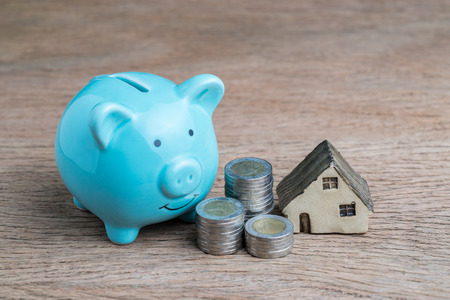 Saving money for house or mortgage loan concept, blue piggy bank, coins stacked and miniature house on wood table.