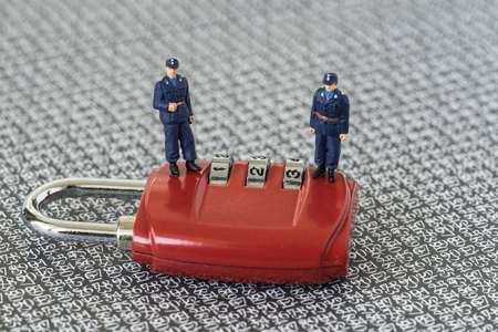 Miniature figure security guards standing on red combination pad lock with the background of computer numbers secret code, hacker and password protection concept.