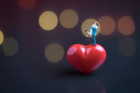 Wedding sweet romantic night concept, happy miniature couple holding and standing on red heart shape with soft low key dark background and beautiful bokeh.