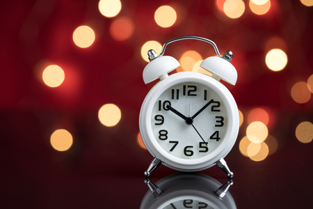 Time for party and wake up to work, white alarm clock with party decoration light bokeh in the red background before midnight. Standard-Bild
