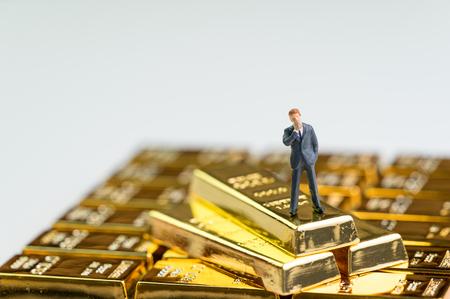 Success finance investment wealth concept, miniature figure businessman standing on stack of shiny gold bar bullions ingot.