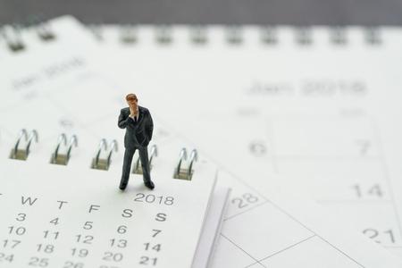 Business appointment, office meeting calendar, miniature businessman thinking and standing on pile of desktop calendars. Standard-Bild