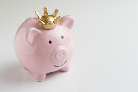 Financial winner or king of money savings concept, smiling happy pink piggy bank wearing a golden crown on top on seamless white table background, best future investment, compound interest deposit. Standard-Bild