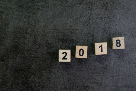 Year 2018 background or story ahead concept with wooden cube block number 2018 on dark black cement texture wallpaper background.