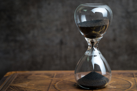 Closed up of sandglass or hourglass on vintage book with dark black loft cement background using as time symbol or business deadline counting down concept.