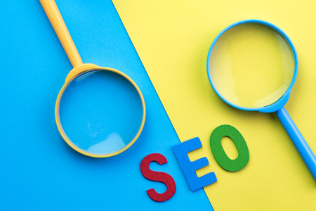 Red, blue and green letters abbreviation SEO with blue and yellow magnifying glass on vivid opposite colors as Search engine optimization concept. Stock Photo