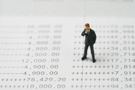Growth of investment, interest compound in savings concept, miniature business man standing and thinking on numbers of money printed on paper bank account book. Stok Fotoğraf