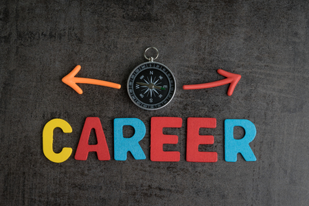 Company career path opportunities concept by colorful wooden alphabets as word CAREER and compass with magnet arrows pointing to left and right on dark black chalkboard cement wall. Banque d'images