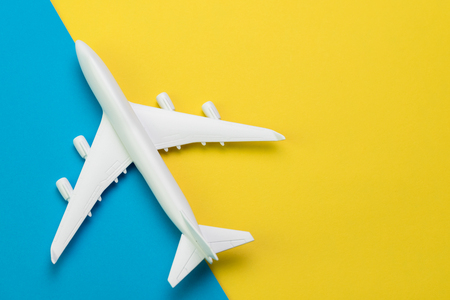 Flat lay, top view of travel and tourism concept, white toy airplane on vibrant and vivid yellow and blue background with copy space. Stock Photo