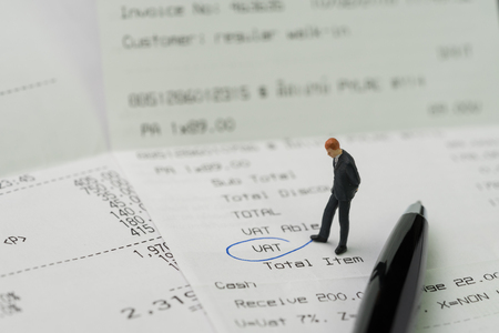 Miniature business man figurine standing on printed payment invoice, bill or receipt and looking at VAT with pen circle using as tax, accounting and business expenses concept. Archivio Fotografico