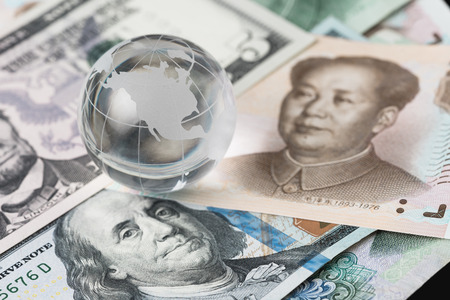 US and China trade barrier, an action by a government that makes trade between the country and other countries more difficult, decoraton glass globe on US dollar and china yuan banknotes. Standard-Bild - 97194071