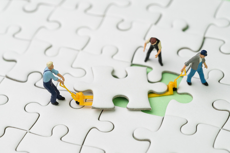 Teamwork, fulfill the missing piece for business success strategy concept, miniature workers team help using the forklift to complete the missing white jigsaw puzzle piece on pastel green background. Foto de archivo