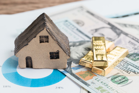 Wealth management or investment asset allocation concept, house, gold bars ingot on pile of US dollar bills on percentage pile chart using in balance risk and rich in financial investment idea. Stock Photo