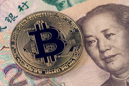 Bitcoin crypto currency banned in China concept, closed up shot of golden physical coin with B sign alphabet on Chinese yuan banknotes.