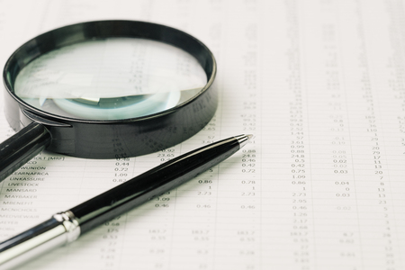 Business perfomance review, searching or chasing for investment return concept, magnifying glass and pen on performance, price numbers report print paper on table.