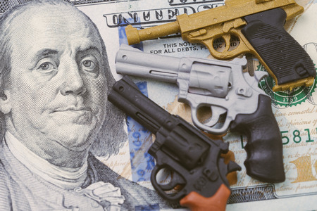 Big money in gun industry, gun control policy in united state of america after many of mass shooting, 3 miniature toy guns poiniting to face of US dallar banknote.