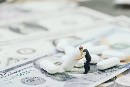 Big money in health care, medical or pharmaceutical industry business concept, miniature worker holding  white tablet pills on US dollar banknotes. Stock Photo