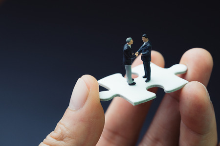 Business success strategy with collaboration, teamwork or negotiation jigsaw key, miniature people businessmen handshaking on white jigsaw puzzle piece in real human hand, dark black background.