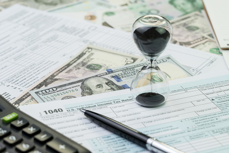 Time countdown for tax deadline concept, hourglass or sandglass with pen on 1040 US individual income tax filling form paper with calculator and US dollar banknotes.
