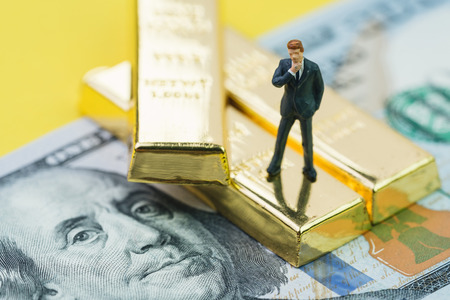 Wealth management or success in investment concept, miniature people businessman standing on gold bullion ingot stack on US dollar banknote money.