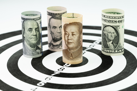 US and China financial trade war tariff strategy concept, US Dollar bank roll surround and targeting Chinese Yuan bank roll at the center of dartboard.