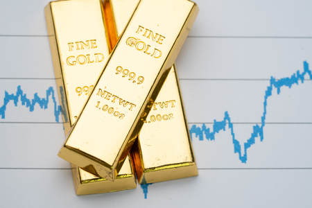 Gold bar, bullion stack on rising price graph as financial crisis or war safe haven, financial asset, investment and wealth concept. Stock Photo