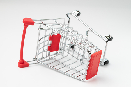 Business accident, product commerce fail or problem concept, closed up of crash red mini shopping cart, trolley on isolated white background. Stockfoto
