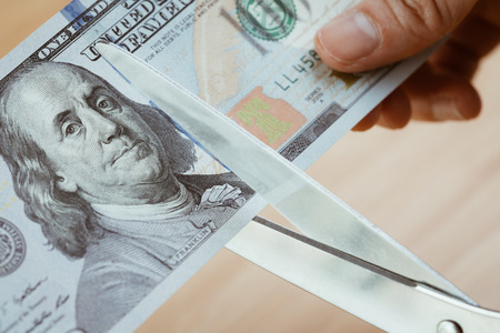 Women hand holding scissors cutting US Dollar banknotes, cut budget, reduce cost or sale at half price and discount.