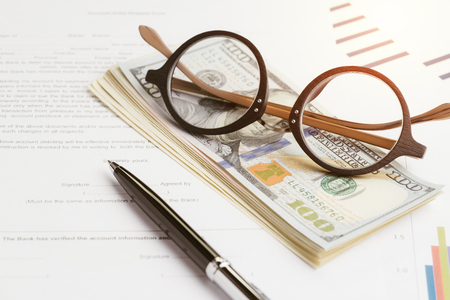 Buy and sell or leasing contract against bank, eyeglasses on pile of US dollar banknotes, printed paper form with pen to sign document with graph and price chart.