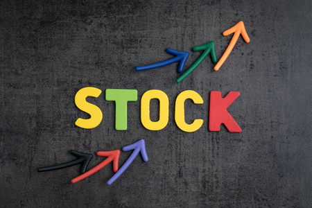 Stock market rising price concept, arrows pointing up as price chart with colorful letters word STOCK on loft cement dark chalkboard, equity investment asset. Stock fotó