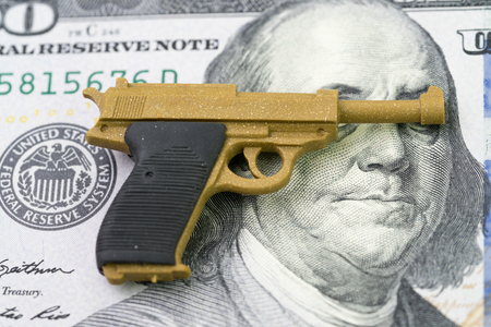 American firearm or gun business with big money concept, gun control policy in united state of America after many of mass shooting, miniature toy guns on Franklin eyes and face of US dollar banknote.