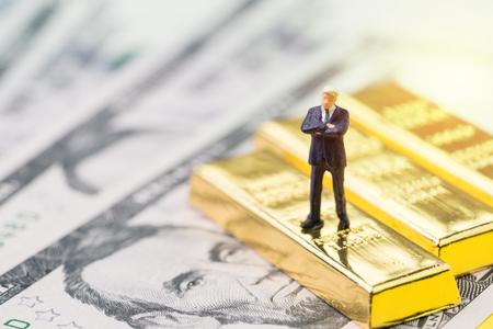 Successo nell'investimento, nella gestione patrimoniale o nel concetto di rifugio sicuro di crisi finanziaria, uomo d'affari in miniatura di persone in piedi sulla pila di lingotti d'oro, lingotti o lingotti sui soldi delle banconote in dollari USA.