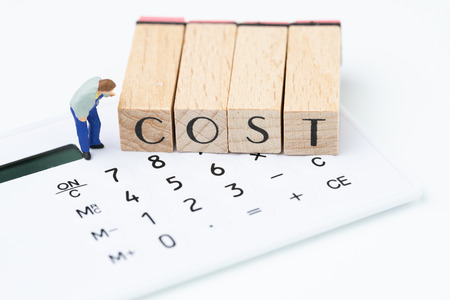 Frais d'entreprise et sensibilisation aux dépenses, figure miniature, l'homme regardant attentivement le bloc de timbres en bois organiser le mot COÛT sur la calculatrice blanche Banque d'images