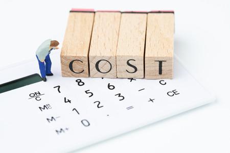 Los costos comerciales y la conciencia de los gastos, la figura en miniatura, el hombre mirando cuidadosamente el bloque de sellos de madera organizan la palabra COSTO en la calculadora blanca. Foto de archivo