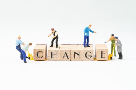 Bedrijfsverandering, transformatie of zelfontwikkeling voor succesconcept, miniatuurmensenfiguur, arbeiders, werknemerspersoneel helpen houten stempelblok verplaatsen om het woord VERANDERING op witte achtergrond te schikken. Stockfoto