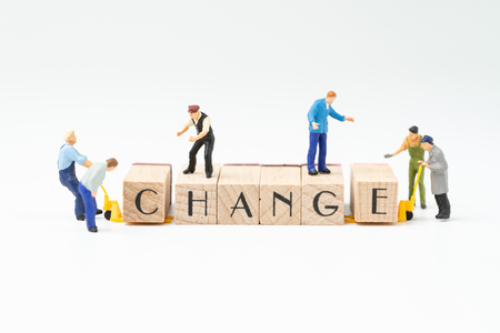 Business change, transform or self development for success concept, miniature people figure, workers, employee staffs help move wooden stamp block to arrange the word CHANGE on white background.