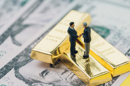 Deal or negotiation in investment, gold, wealth management concept, miniature people rich businessman shaking hand on gold bar, bullion or ingot stack on US dollar banknote money.