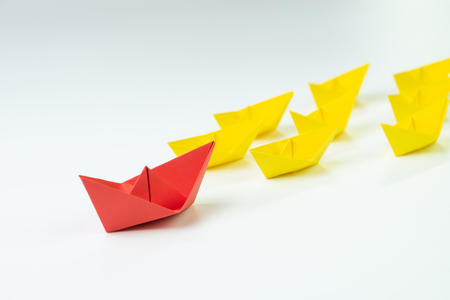 Leadership, influencer, KOL, key opinion leader concept, big red paper ship origami in front of others followers small yellow fleet.