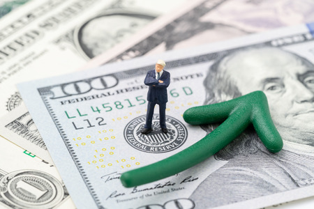 FED consider interest rate hike, world economics and inflation control, miniature businessman leader standing on US Federal Reserve emblem on dollars banknote with green arrow rising up.