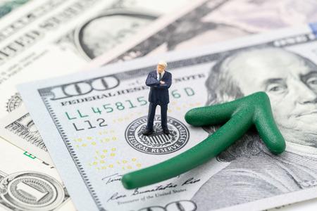 La FED considera l'aumento dei tassi di interesse, l'economia mondiale e il controllo dell'inflazione, il leader in miniatura dell'uomo d'affari in piedi sull'emblema della Federal Reserve statunitense su una banconota in dollari con freccia verde che sale.